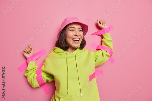 Fotografiet Positive Asian woman laughs happily plastered to wall with sticky tapes wears panama and hoodie feels not free isolated over pink background
