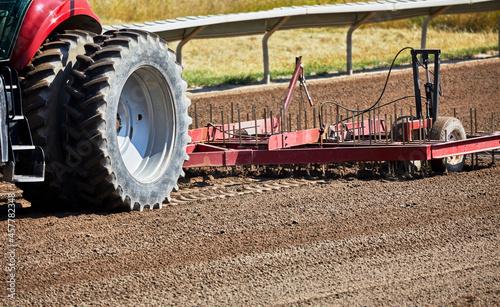 Fotografie, Obraz Tractor pulling a harrow on a dirt track