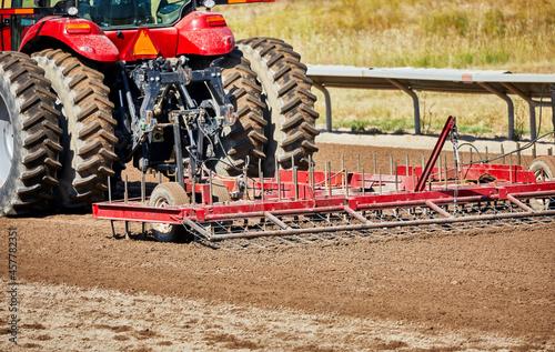 Fototapeta Tractor pulling a harrow on a dirt track