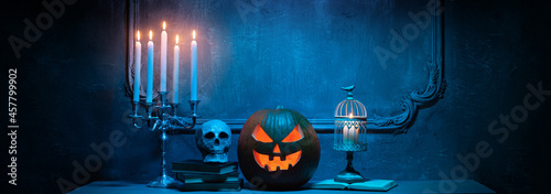 Fotografiet Scary laughing pumpkin and old skull on ancient gothic fireplace