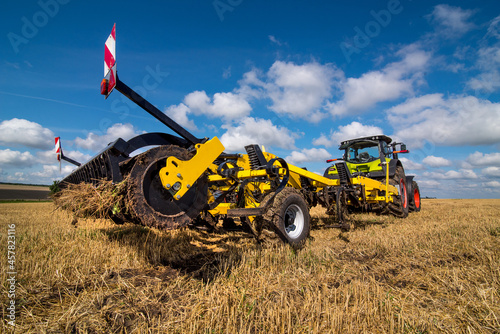 Fototapeta tractor with a heavy disc harrow on the field with cloudly sky