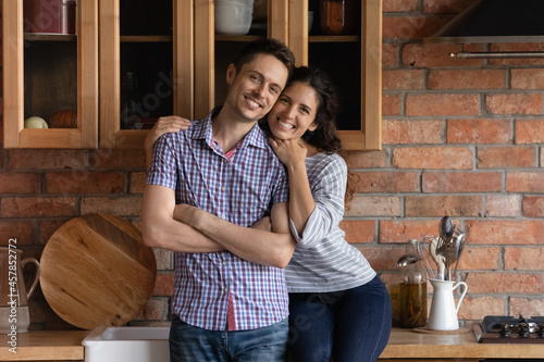 Foto Portrait of smiling bonding millennial generation hispanic family couple posing in wooden kitchen, feeling excited of moving in renovated stylish cottage house0, real estate ownership concept