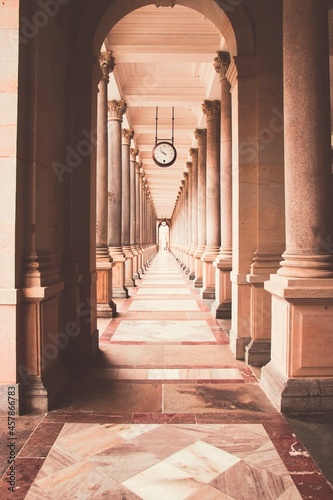 A view into the historical colonnade with clock above at spa city Karlovy Vary, Fotobehang