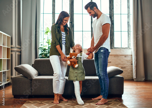 Fotografia, Obraz Mom and Dad help their little daughter with a broken leg with rehabilitation, teach her to walk again
