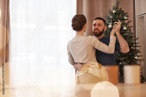 Fototapeta Happy young couple dancing waltz in cozy living room with Christmas tree