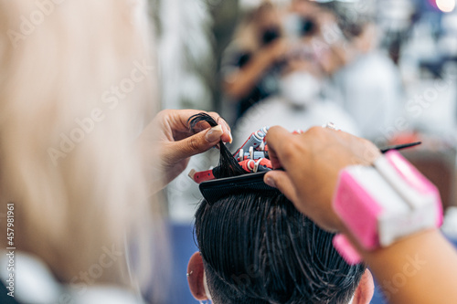 Canvas Photo with copy space of a hairdresser using a comb to curl the hair of a man