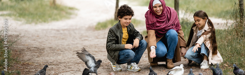Fotografie, Obraz Muslim mother and kids feeding birds in park, banner