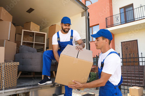 Fototapeta Workers unloading boxes from van outdoors. Moving service