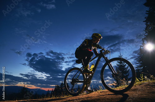 Canvastavla Young man cycling bicycle under beautiful night sky