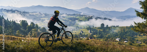 Fotografiet Man riding bicycle on grassy hill and looking at beautiful misty mountains
