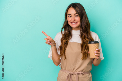 Canvas-taulu Young caucasian store clerk woman holding a takeaway coffee isolated on blue background smiling and pointing aside, showing something at blank space