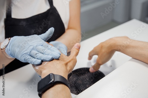 Fotografering Young man gets professional manicure care for nail in spa salon, master applies