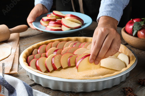 Canvastavla Woman putting apple slices into dish with raw dough at wooden table, closeup