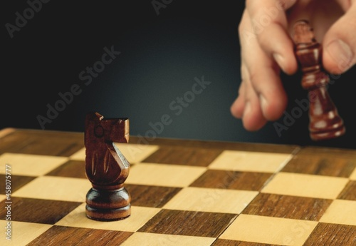 Tela Human hand of businessman wearing suit moving chess figure in competition success play