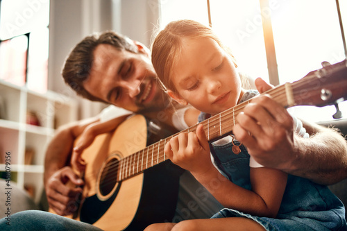Obraz na plátně Happy dad teaches his cute daughter to play the guitar while sitting on the sofa in the living room at home