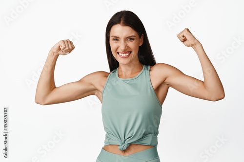 Strong beautiful woman flexing biceps, showing muscles on arms and smiling happy Fotobehang