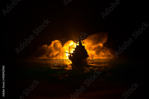 Canvas Print Silhouettes of a crowd standing at blurred military war ship on foggy background