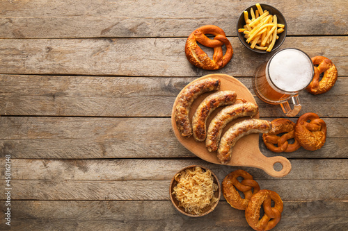 Canvastavla Mug of cold beer, board with Bavarian sausages and snacks on wooden background