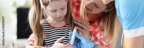 Little girl has doctor taking blood test with lancet Fototapeta