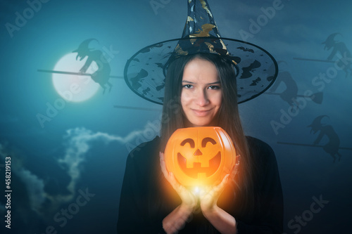 Wallpaper Mural halloween witches party,magical sorceress in a hat with a burning pumpkin at mid