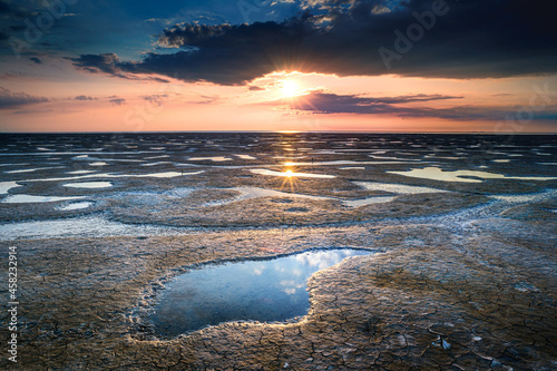 Fotografie, Obraz Shot of a sea coast spangled by stone with sunrise reflecting on the wet sand in