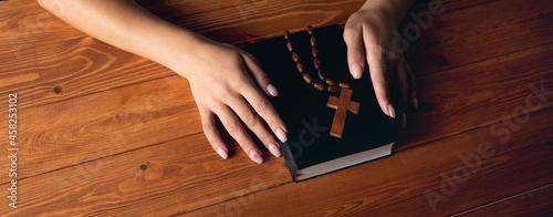 Obraz na plátně woman praying on book holding cross