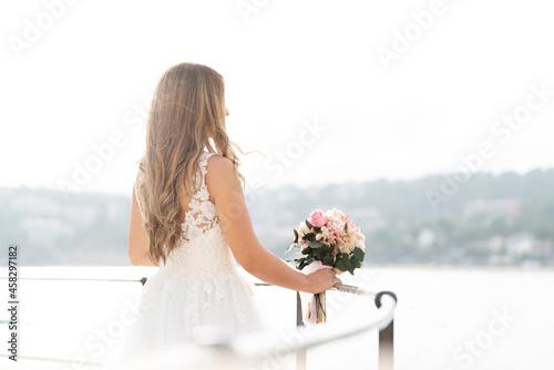 Fotografie, Obraz Brunette bride in white dress looking at the sea