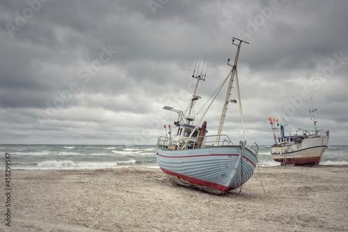 Fotografie, Obraz Zwei Fischerboote liegen am Strand bei Ebbe