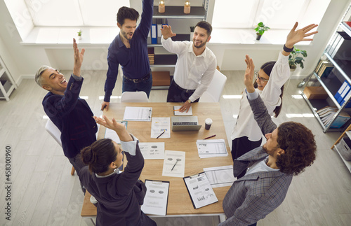 Obraz na plátně Excited diverse team celebrating corporate business success with raised hands standing around office desk overhead view