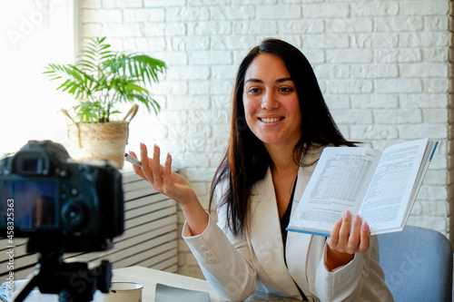 Wallpaper Mural Young brunette woman wearing white jacket recording a video lesson on a camera