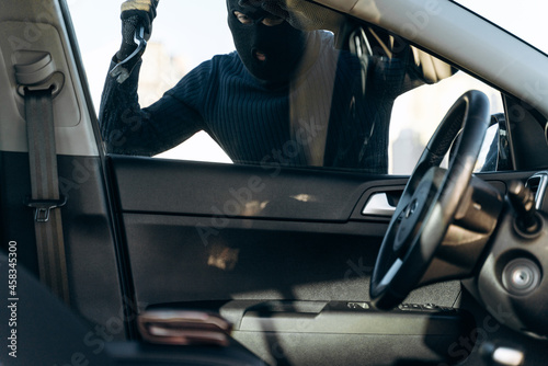 Photo View from the car at the man dressed in black with a balaclava on his head preparing breaking with crowbar the glass of car before the stealing