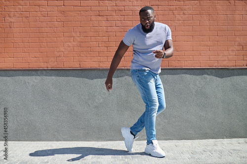 Canvastavla A dark-skinned man in a white tshirt and jeans feeling good