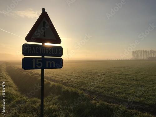 Fotografie, Obraz Road Sign On Field Against Sky During Sunrize