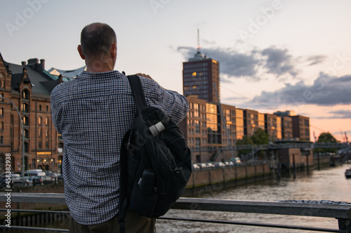 Fotografiet Rear shot of a man standing by a balustrade watching the cityscape of Hamburg, G