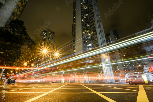 Fototapeta Light Trails On City Street By Buildings Against Sky At Night In Hong Kong