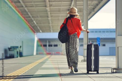 キャリーケースと歩く女性 Fototapet