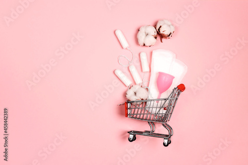 Obraz na plátně Shopping cart with menstruation period accessories on pink background