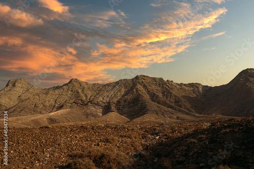 Fotografiet Rocky hills under sunset sky