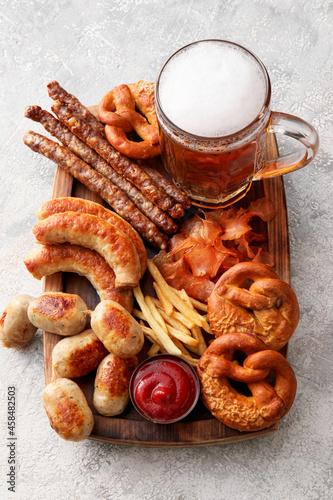 Obraz na plátně Mug of cold beer, wooden board with Bavarian sausages and snacks on light background