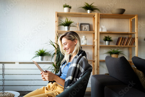Fototapeta Happy young woman using tablet pc in loft apartment