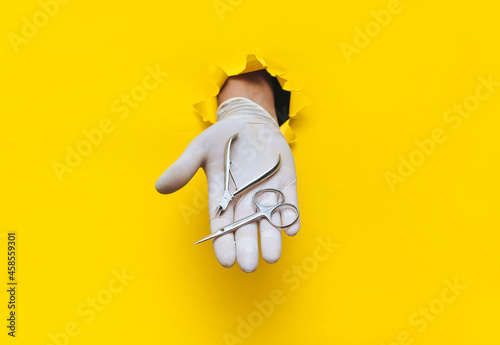 Fotografering A man's hand in a white medical glove holds a nipper and scissors for a pedicure (manicure)