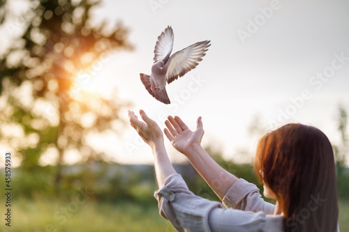 Dove flies into the hands of a woman during prayer as a symbol of hope.