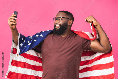 Canvas Photo of cheerful american african man protester raise american national flag black people revolution love all human beings express unity solidarity isolated over pink background