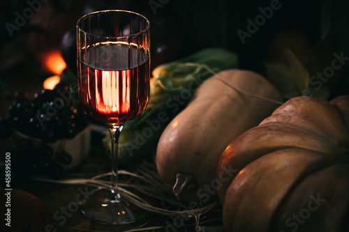 Fényképezés Glass of rose wine or cider in wine glass in a moody autumn vintage atmosphere
