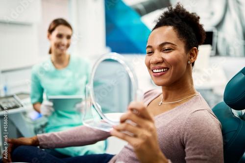Fototapeta Happy black woman looking her teeth in a mirror after dental procedure at dentist's office