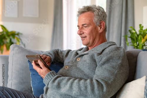 Billede på lærred Happy caucasian senior man sitting on sofa and using tablet