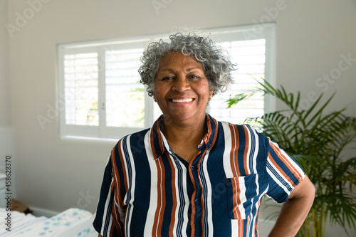Happy african american senior woman standing in bedroom and looking at camera