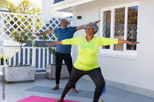 Focused african american senior couple practicing yoga in garden