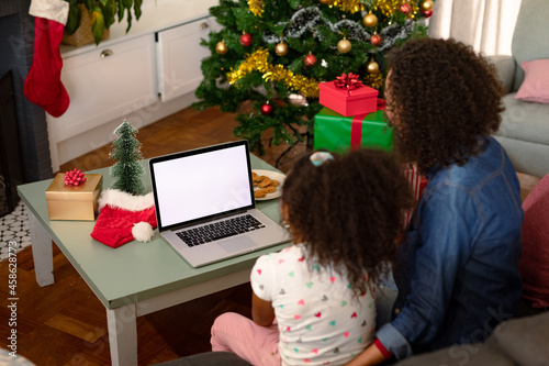 Back view of african american mother and daughter using laptop with copy space on screen