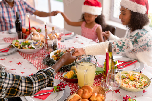 Happy multi generation family wearing santa hats, praying together, having christmas meal